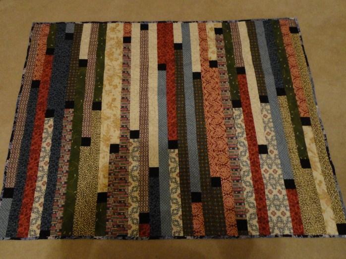 zippy strippy quilt with black blocks